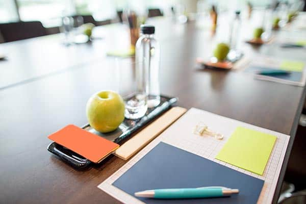 Closeup of glass, apple and stationery set on conference table. High angle view.